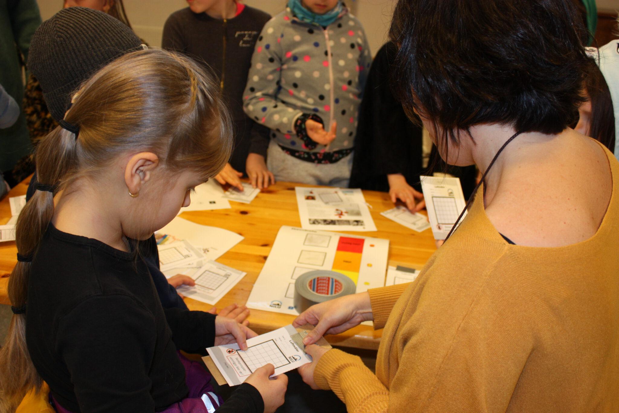 Seniorforsker Núria Castell viser fjerdeklassingen Elin Bakkerud Depuis hvordan man gjør klar luftmåleren til bruk.