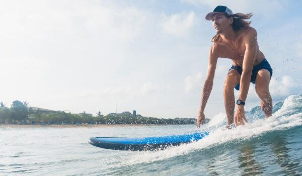 Mann i shorts på surfebrett
