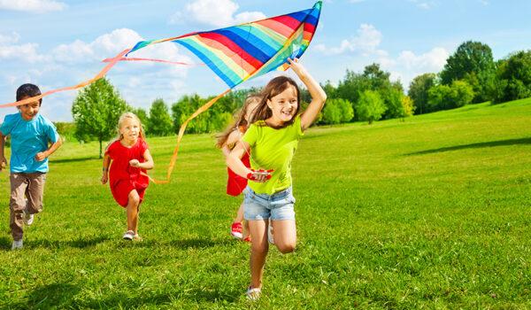 Barn leker med drage i solskinn
