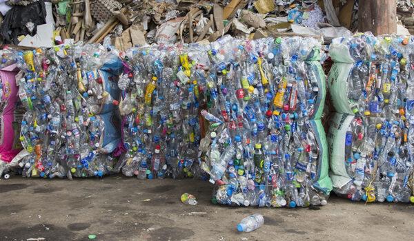 Store bunter med komprimerte plastflasker på et resirkuleringsanlegg i Thailand